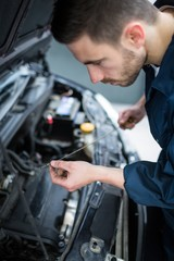 Mechanic checking the oil level in a car engine