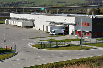 Modern logistics center, white van and trailers standingon ramp