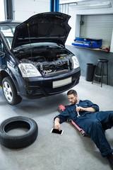 Mechanic using digital tablet while repairing a car