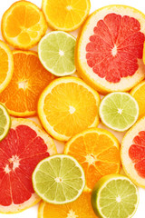Surface covered with citrus sliced fruits over white isolated background