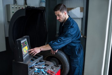 Mechanic prepares a tyre balance machine