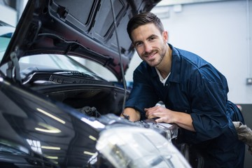 Mechanic smiling at camera while examining car engine