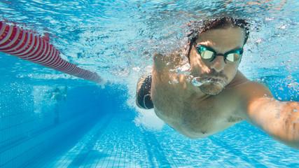 Mann krault im Freibad auf Schwimmbahn - Unterwasseraufnahme