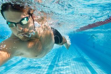 Mann schwimmt Kraul im Freibad - unter Wasser