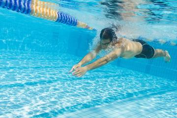 Schwimmer taucht und gleitet unter Wasser