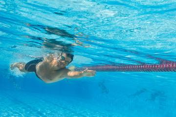 Lachender Mann schwimmt im Freibad - Unterwasseraufnahme