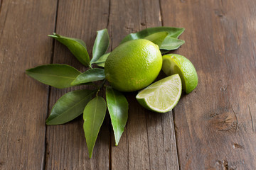 Fresh limes with leaves on a wooden table