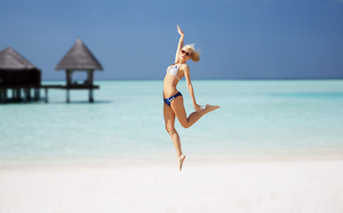 happy young woman jumping over exotic beach