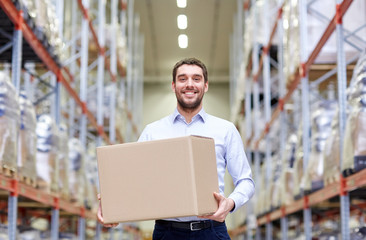 happy man with cardboard parcel box at warehouse