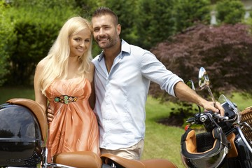 Happy casual couple with scooter in outdoor garden