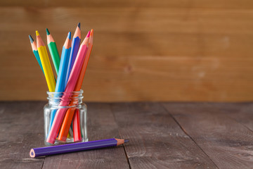 Color pencils in glass jar on wooden background