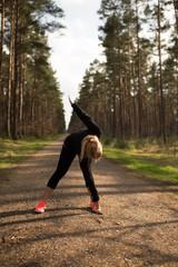 Sportliche Frau macht Dehnübungen auf einem Schotterweg im Wald