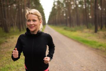 Joggerin läuft auf einem Schotterweg im Wald