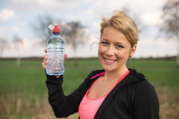 Lächelnde blonde Joggerin steht auf einem Feld und hält eine Wasserflasche