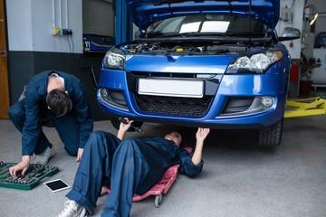 Mechanics repairing a car
