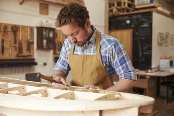 Man working on wooden surfboard in workshop