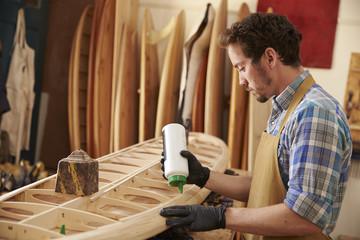 Carpenter gluing bespoke wooden surfboard in workshop