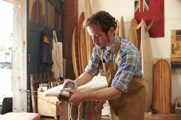 Carpenter planing bespoke wooden surfboard in workshop