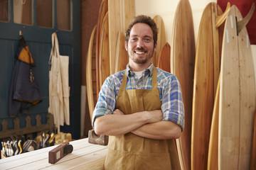 Portrait Of Carpenter Making Bespoke Surfboards In Workshop
