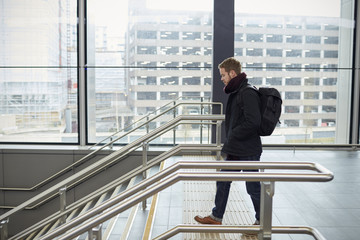 Young Man Walking Down Stairs In Railway Station