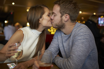 Romantic Couple Sitting And Talking In Wine Bar Together