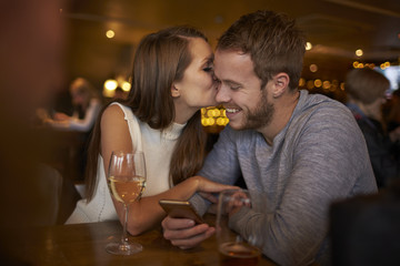 Young woman kissing man while sitting in bar