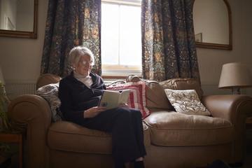 Senior Woman Sitting On Sofa Reading Book At Home