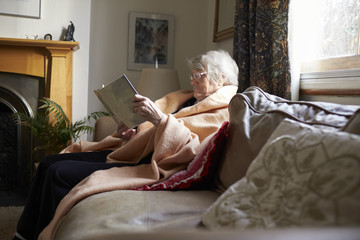 Senior Woman Sitting On Sofa Reading Book Wrapped In Blanket