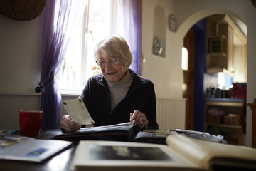 Senior Woman Looking Through Photo Album At Home
