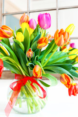 Bouquet of spring colorful tulip flowers in glass vase.
