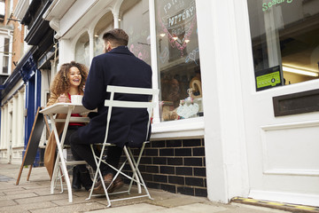 Couple Sitting Outside Cafe Enjoying Coffee And Snack