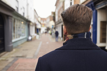 Rear View Of Young Man Walking Down Urban Street