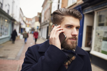 Young Man Walking Down Urban Street Using Mobile Phone
