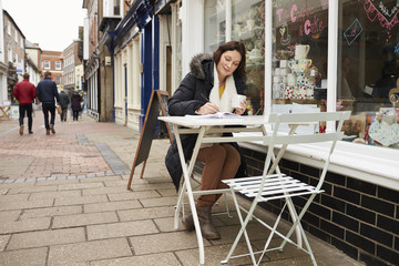 Mature Woman Sitting Outside Cafe Whilst Working