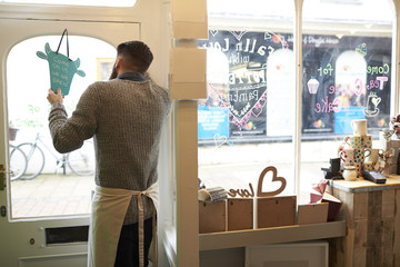 Male Owner Of Coffee Shop Turning Open Sign