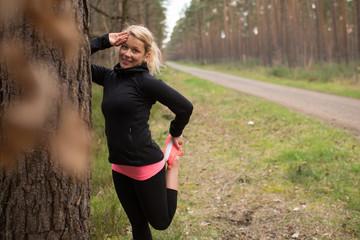 Joggerin macht verschiedene Dehnübungen an einem Baum im Wald