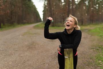Joggerin jubelt voller Power und Energie auf einem Waldweg