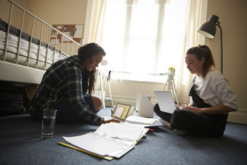 Two Female Students With Laptops Studying In Bedroom