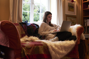 Young Woman At Home Sitting On Sofa Using Laptop