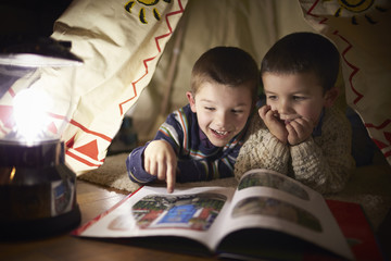 Two Young Boys Reading Inside Tent Set Up Indoors