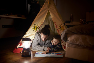 Father And Son Reading Inside Tent Set Up Indoors