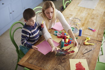 Mother and son painting on kitchen table at home