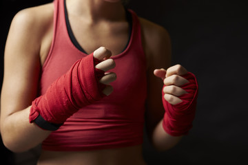Midsection of woman with fists wrapped in preparation for boxing training