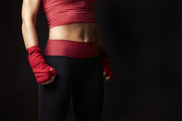 Mid-section of woman, fists wrapped in preparation to box