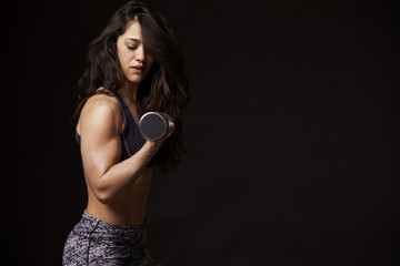 Side view of muscular young woman working out with dumbbells