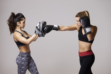 Young woman boxing training with her female sparring partner