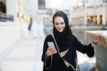 Arabian woman typing on smart phone and smiling.
