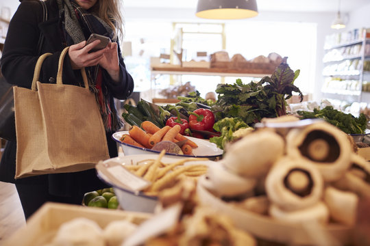 Woman Looks At Shopping List On Mobile Phone In Delicatessen