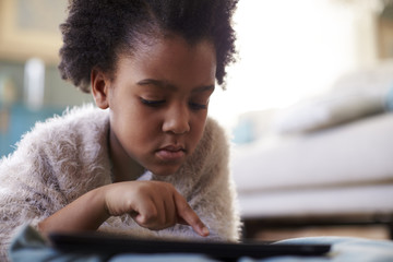Young Girl Using Digital Tablet At Home