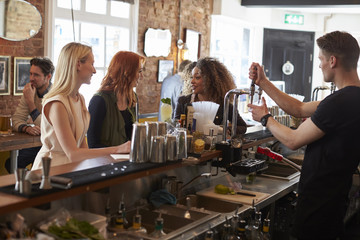 Group Of Female Friends Enjoying Drink In Cocktail Bar